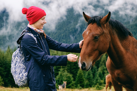 Young female tourist bonding with new friend, a horse grassing in the valley, touching its face, in the Carpathians on a foggy day in Autumn.
