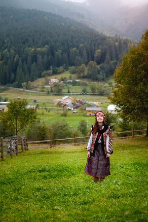 Beautiful dreamy caucasian female wearing ethnic ukrainian clothing of Carpathian women posing on the mountain village background in Autumn.