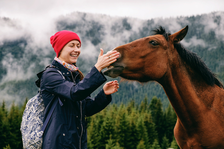Young smiling female tourist bonding with new friend, a horse grassing in the valley, touching its mouth, getting to know each other in the Carpathians on a foggy day in Autumn. Stock Photo