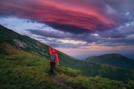Astonishing landscape of Carpathian pinkish sky at sunset in Summer and a happy hiker, shot from back, celebrating beauty of nature by trying to reach it with her arm.