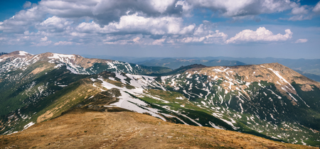 Beautiful panorama of Carpathian peaks covered with snow leftovers on a sunny day in Spring. Wanderlust travel concept. Reklamní fotografie