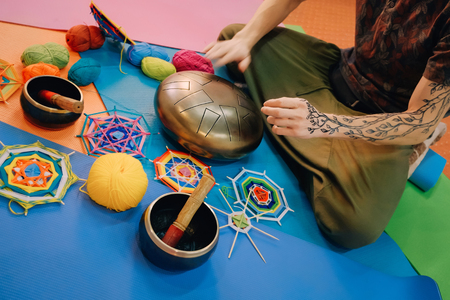 Young caucasian man with henna tattoo on his hand playing hang drum with fingers sitting on a blue mat in class in front of yarn and knitted mandalas