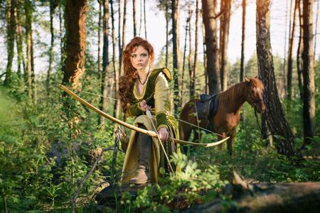 Mujer medieval guerrera con arco de caza en el bosque misterioso
