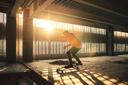 Extreme street sport. Hipster man jumping and riding on long board at an abandoned building at sunset. Image with grain Stockfoto - 105232121