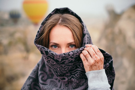 Closeup woman portrait with beautiful eyes and mehendi henna tattoo on hand in Cappadocia landscape and hot air balloon