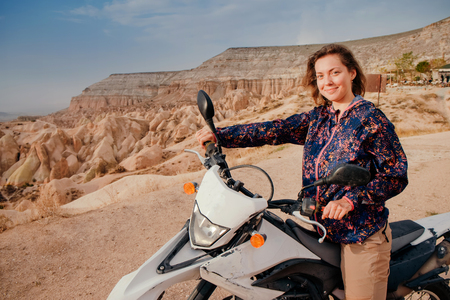 Beautiful woman riding and explore Cappadocia mountain valley landscape on enduro motorcycle at sunset. Travel to Turkey