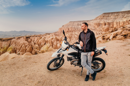 Handsome man riding and explore Cappadocia mountain valley landscape on enduro motorcycle at sunset. Travel to Turkey Imagens