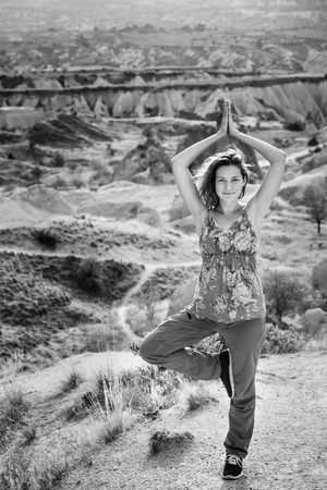 Woman practice tree yoga pose in nature. Black and white Cappadocia mountain landscape with beautiful sky
