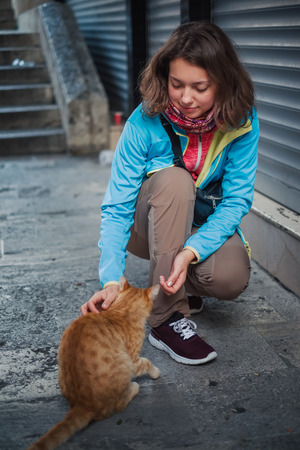 Portrait of beautiful woman that paying with red homeless cat. Love and fun emotion for pets