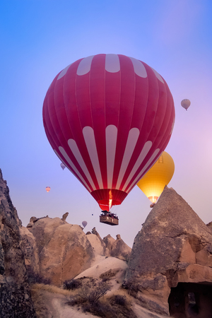 Close-up colorful big hot air balloons flying over beautiful Goreme village landscape at sunrise. Cappadocia is famous travel destination with beautiful limestone mountains, Turkey