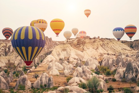 Beautiful hot air balloons flying over beautiful Goreme landscape at gold sunrise. Cappadocia is famous travel destination with limestone mountains, Turkey Stockfoto