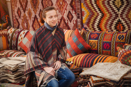Traveler woman see traditional turkish textile on Grand bazaar in Istanbul, Turkey Imagens