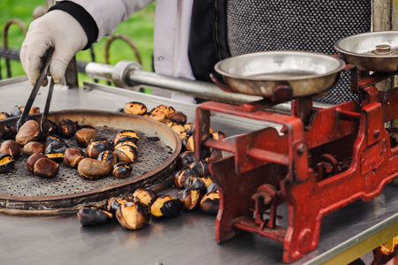 Seller with cart of grilled chestnuts on the street on Egyptian bazaar in Istanbul, Turkey Stock Photo