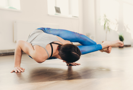 Young woman doing yoga exercises and fitness stretching at white studio at the morning