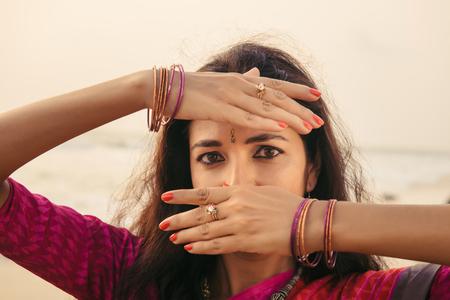 Portrait of beautiful indian woman in red saree dancing traditional Bharatanatyam dance