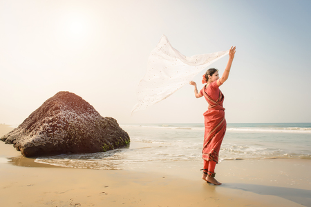 Indian woman feel freedom and standing near the beach in traditional saree clothing with white tissue in the hands