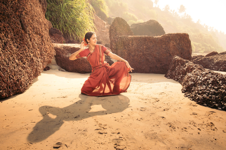 Indian classical dance Bharatanatyam performed by beautiful woman in traditional clothes at sunset