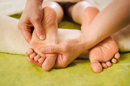 Traditional foot massage. Beautiful woman enjoying a treatment in a spa center Stock Photo