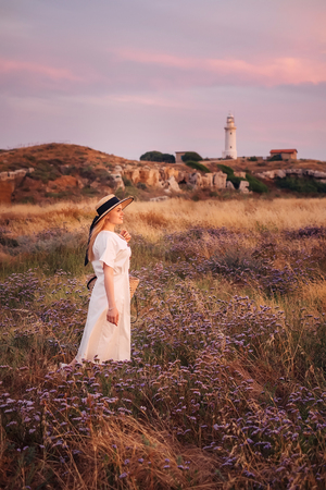 Beautiful blonde woman in white dress travel to Cyprus and enjoying summer nature near lighthouse beach. Freedom concept