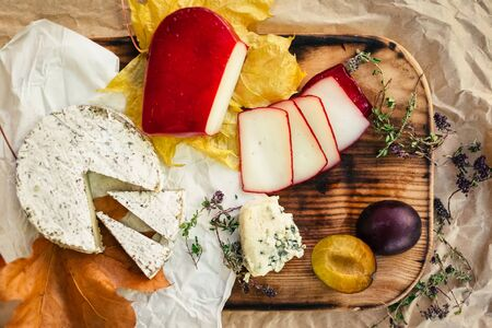 Set of aged Cheese, brie, camembert with fruit and herbal on wooden and craft paper background Stock fotó