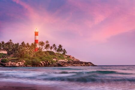 Lighthouse on the cliff surrounded by palm trees and blurred sea waves on the Kovalam beach. Kerala, India Foto de archivo