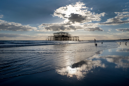 brighton: Brighton west Pier at sunset with a solitary man walking into the sea Editorial