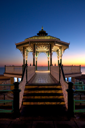 Brighton Victorian bandstand at sunset, also known as birdcage bandstand, the bandstand newly refurbished and is lit with white light and there is a beautiful sunset behind, newly refurbished Stock Photo