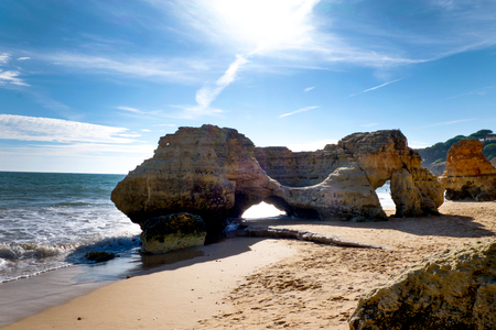 Big rock formation on Olhos De Agua beach, the sun is behind and shining through the natural holes in the rock, this rock formation sits in the middle of the sandy beach, it is very typical of the beautiful rock formations on beaches in the Algarve, Portu