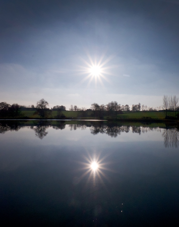 sun shining on a lake with a thin line of green fields in the middle, the sky, sun fields and trees are reflected in the lake duplicating the image in the lake