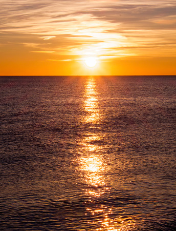 yeloow: low sunset sun with sunbeam in the centre casting long highlight from the sun accross the sea, the sea is bottom two thirds of photograph and the sunset sky is one third of photograph