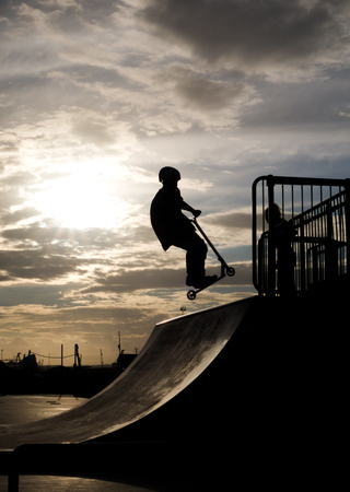 halfpipe: boy on childâ??s scooter in mid air jump on halfpipe in scate park, sun and sky in background