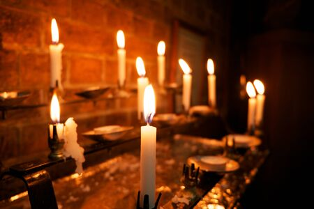 iluminate: 8 burning white candles in a church, the foreground candle is in focus and the others are out of focus,