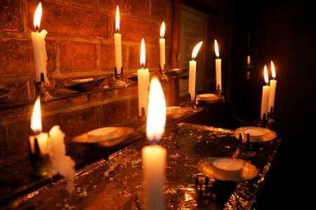 iluminate: 8 burning white candles in a church, the foreground candle is out of focus and the others are in focus, Stock Photo