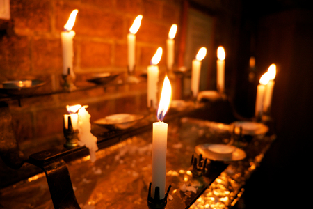 8 burning white candles in a church, the foreground candle is in focus and the others are out of focus,
