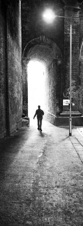 silhoutted: Man walking through large industrial brick arch, bright light and long shadows through brick arch, black and white photograph