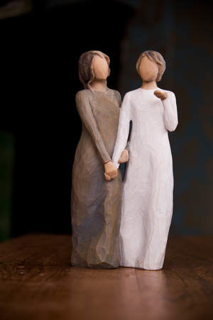 paper sculpture: wooden statue 30cm meters high, of two womwn holding hands affectionately, statue is on a wooden surface with a black background, the statue of the women is carved wood, one women is wearin a long green dress and the other a white dress, this staue could