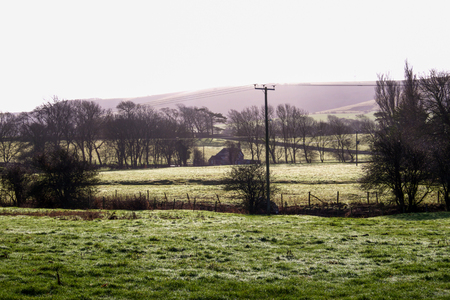 frosty green field in the foreground, farmhouse in the middle, south downs behind, british rural scene