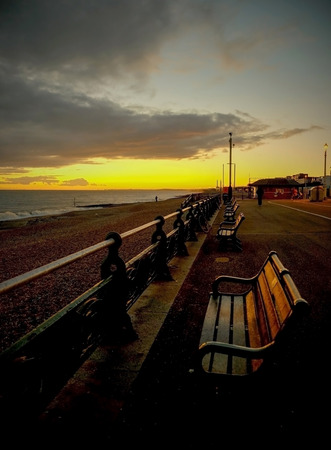 a line of wooden seats along a seafront promenade, the first bench is large in the foreground of the image, the benches are on a concrete promenade on Brighton and Hove seafront, old ornate railings run down the centre of the image on the left of the rail Stock Photo