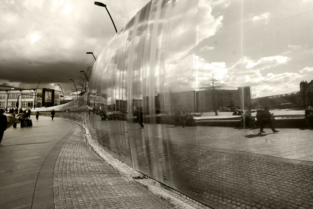 reflective metal mirror sculpture about 200 yeard in length water running down sculpture, built to reflect Sheffield's history of metal, water and light, the sculpture is situated in a pedestrian precinct called Sheaf square outside Sheffield ttrain stati