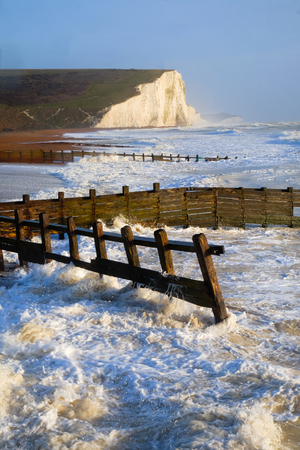 rough breaking white waves against wooden sea groynes in the forground looking accross sweeping pebble beach to white cliffs in background blue sky