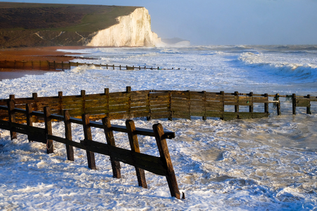 Cuckmere Haven Sussex beach in the foreground is the beach and in the background are the white cliffs of the Seven Sisters cliffs, infront of the cliffs is the sea the beach in the foreground has pebbles, sand ,rocks and wooden sea groynes on it the sky is blue Standard-Bild
