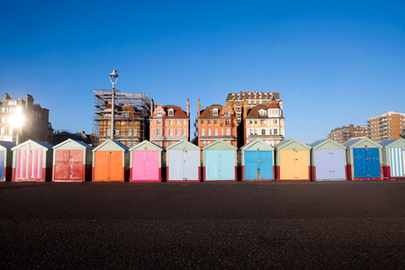 Brighton seafront 13 multi coloured beach huts, on Brighton beach promenade behind is blue sky and 3 victorian buildings, one of the buildings has scaffolding all over it, infront is the concrete promenade.