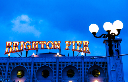 Brighton Pier bright red and yellow neon sign saying Brighton Pier, ontop of Brighton Pier entrance with a street lamp behind, taken at night, blue hue to photograph where not lit Editorial