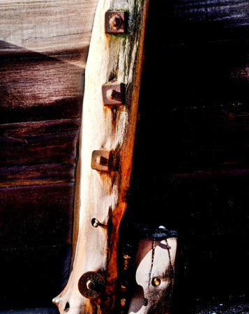 Wooden, weathered sea defence wall, three gnarled planks of wood running horizontally accross the image and a thick vertical wooden post with three big rusty bolts on it, lots of wooden texture Standard-Bild