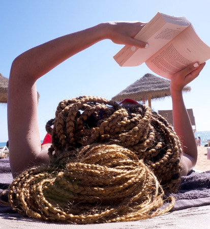 Close up of the back of a womans head of light brown color braided hair, she is lying on a sunbed on a her back reading a book, her arms are stretched above her holding the book, in the background is the beach and sun umbrellas