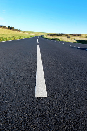 A camber on grey asphalt country road with strong white lines in the middle, the low view point makes the road and white lines big in the foreground leading to the road curving off into the distance of grass rolling hills.