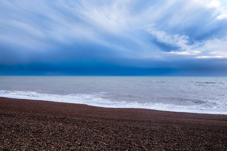 Brighton beach, Sussex, United Kingdom, at the bottom a line of red pebble beach in the middle the sea and at the top of the image a deep blue dramatic stormy sky