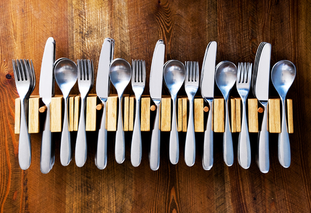 lots of knives forks and spoons staked in a line in five wooden cutlery holders on a wooden table top, color photograph