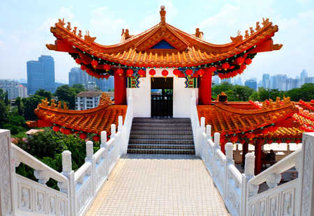 The Bright colours of The Thean Hou Temple in Kuala Lumpur, 6 tiered temple to the chinese goddess Mazu, located in the district of Robson Heights, the sky line of the new high rise city is in background creating a contrast of old and new