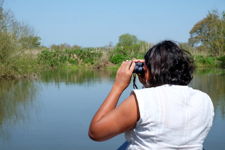 53 year old Asian woman sitting at the front of a canoe turning sideways to the left looking through a pair of binoculars for wild life, the canoe is on a blue river with green vtrees and grass on eit